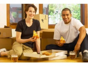 couple having pizza and beer in new home - home